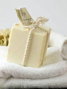 Photo d'un cube de savon écru posé sur une serviette de toilette blanche