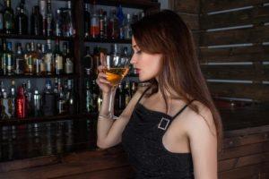 image d'une femme qui va boire un verre d'alcool